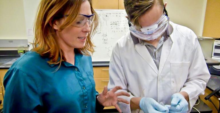A professor stands next to a student in a lab coat, explaining something. Both are wearing safety goggles.